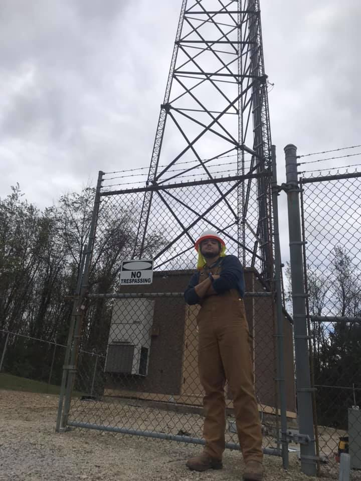 electrical worker standing in front of an electrical tower