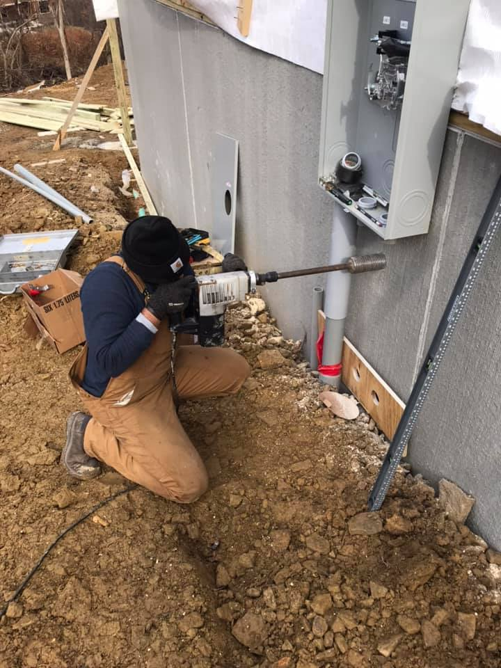 man drilling a hole through wall