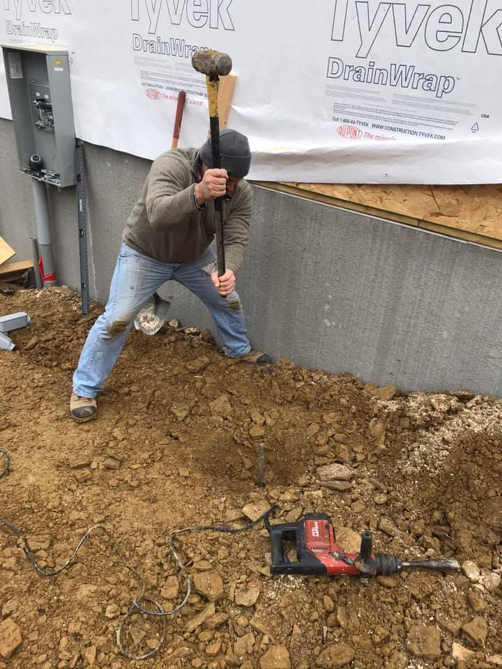 man striking a post into ground with a hammer